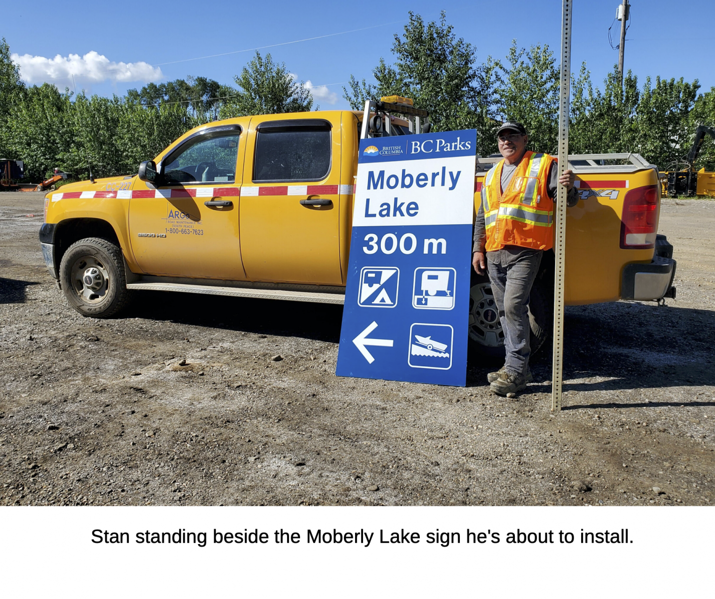 Stan standing beside the Moberly Lake sign he's about to install.
