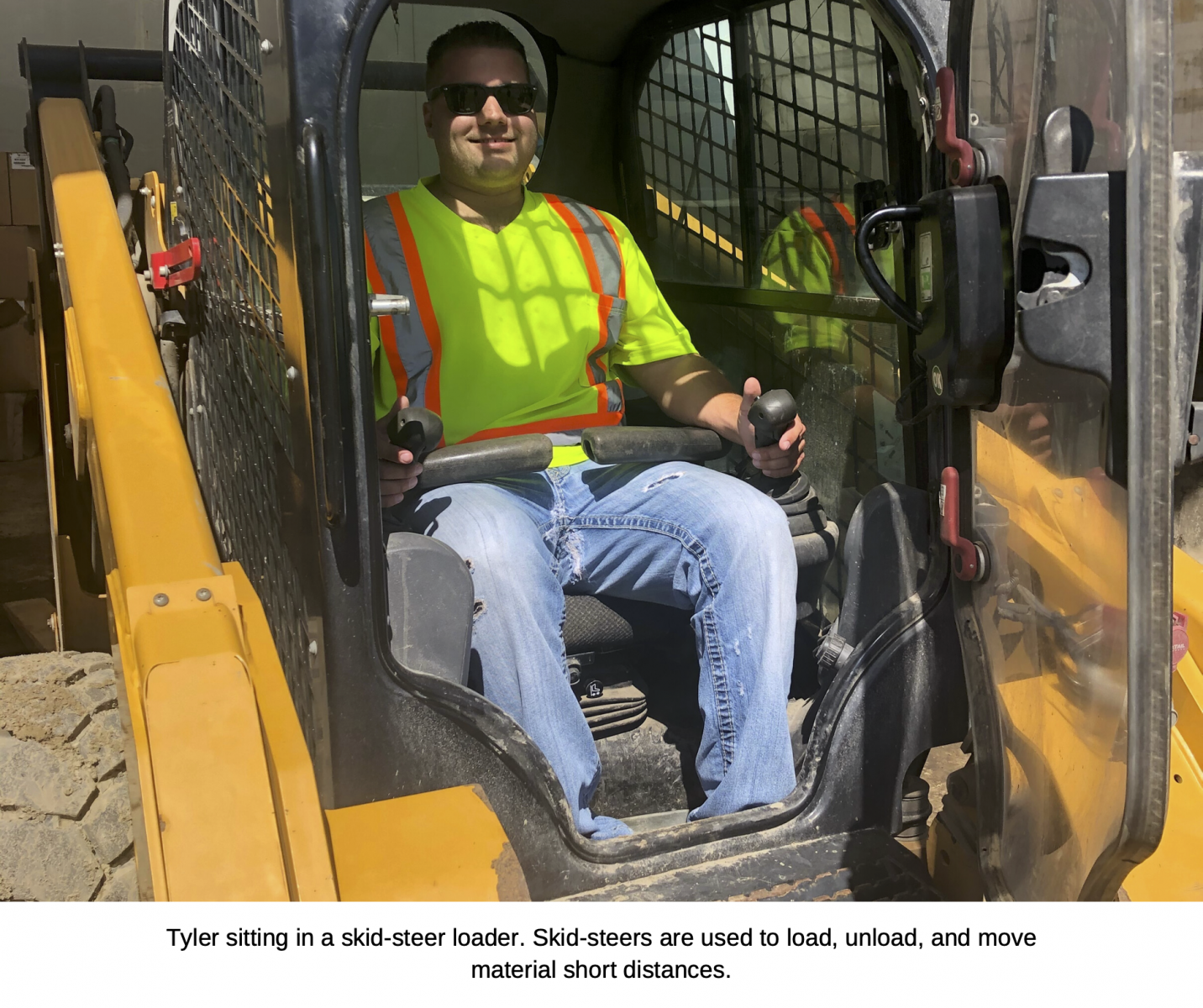 Tyler sitting in a skid-steer loader. Skid-steers are used to load, unload, and move material short distances.